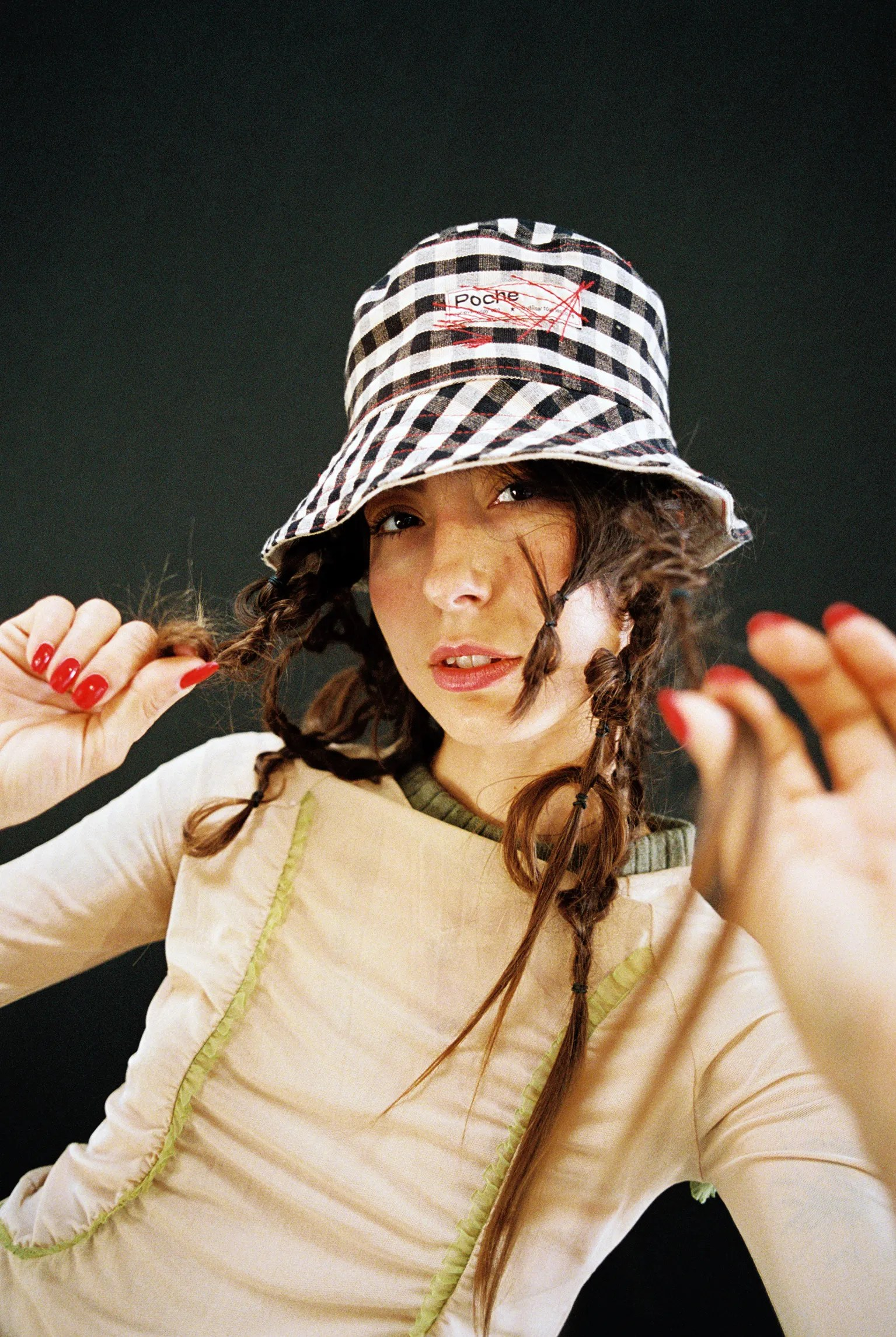 A girl wears a gingham bucket hat and plays with her hair