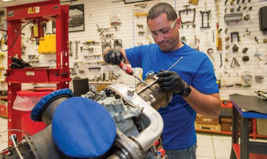 Nestor Lopez reinstalls the cases on a Rolls-Royce M250 engine compressor.