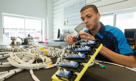 In the wire harness shop, Jonathan Ferrer tests a completed harness assembly for CASA 212.