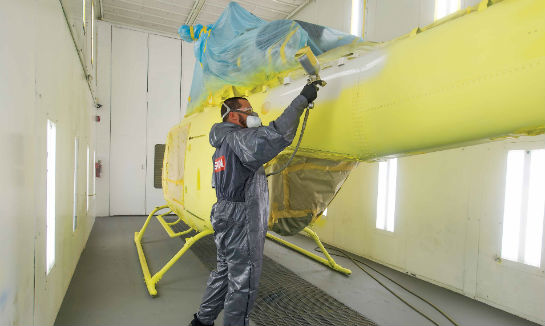 Inside the paint booth, Xavier Quiñonez sprays a primer coat on a new Bell 429.
