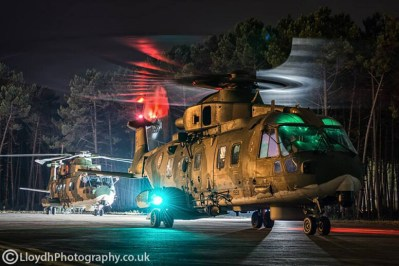 Two AgustaWestland AW101 Merlins operated by Portugal's 751 Squadron on the tarmac outside of the main hangar at Ovar air base. The aircraft with the rotors still running has just returned from a night mission during Exercise Hot Blade 2014.