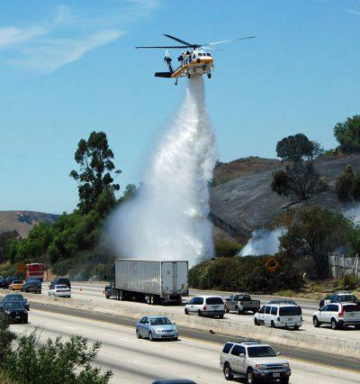 An L.A. County Fire Department Firehawk drops water along the 101 Freeway in Calabasas