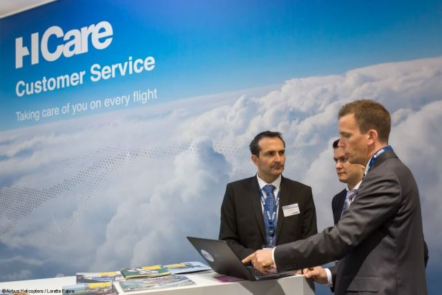 Three men stand next to a computer with HCare logo on wall behind them