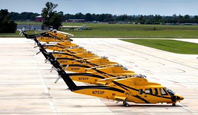 Several helicopters rest on the ground, in a row.