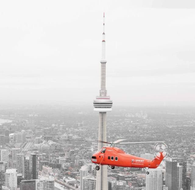 The S-58ET flies above the iconic skyline of downtown Toronto, with the CN Tower and Rogers Centre in the background. The aircraft is the only one of its type currently flying in Canada.