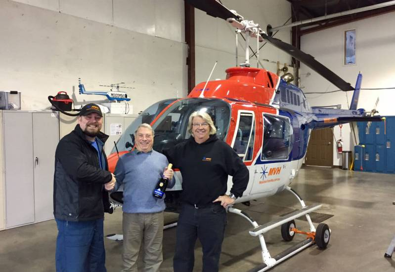 """Richard Alzetta (middle) """"semi-retired"""" in 2011, but still instructs part-time, flying about 300 to 400 hours a year. Here, he celebrates his landmark with Paul Bergeron (right), Mountain View Helicopters president. Mountain View Helicopters Photos"""
