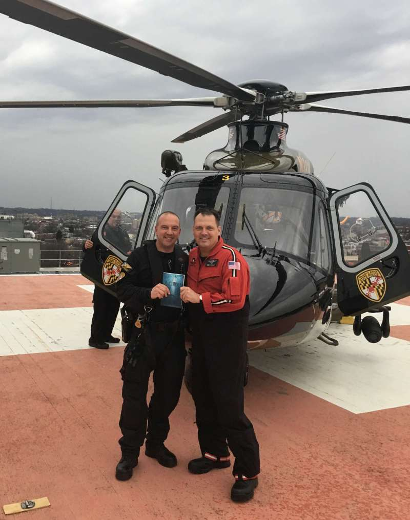 Dave Svites, left, was on the Maryland State Police helicopter Trooper 2 the night of Jonathan Godfrey's rescue. He recently visited Godfrey at work to receive a signed copy of Max Impact. Photo courtesy of Jonathan Godfrey