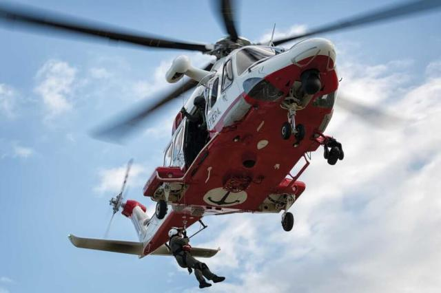 A rescue swimmer is lowered from the AW139 during a training exercise at a small airfield.