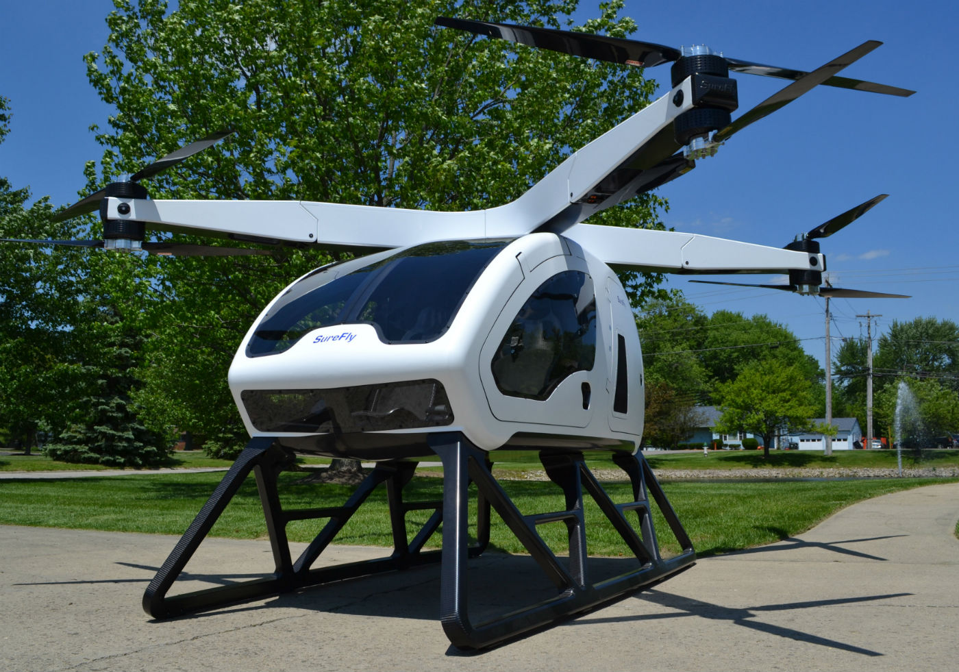 "The SureFly features a two-seat cabin that more closely resembles an automobile chassis than a helicopter airframe, with lift provided by eight single-blade propellers  one above and one below each of four foldable arms that reach out in an ""X"" from above the center of the cabin. Underneath the cabin are two simple skids. Workhorse Photo"