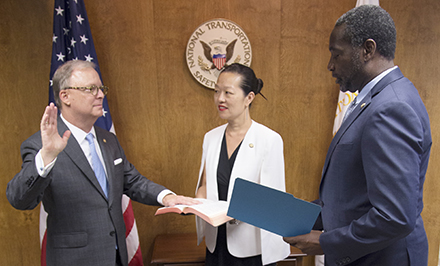 Man is sworn in with woman and other man looking on.
