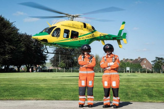 A critical care paramedic and trainee CCP flanked by the charity's Bell 429 at Wiltshire's home base.