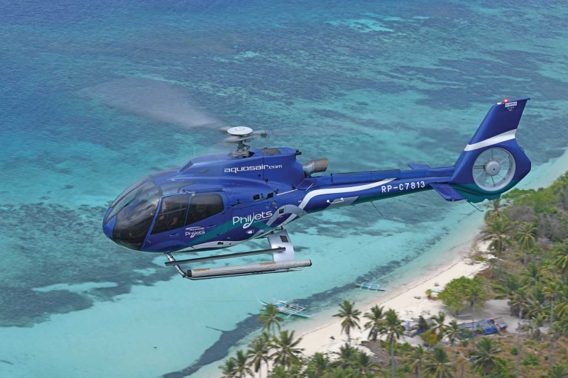 A PhilJets Airbus H130 flies over a picture-perfect piece of Philippine coastline.