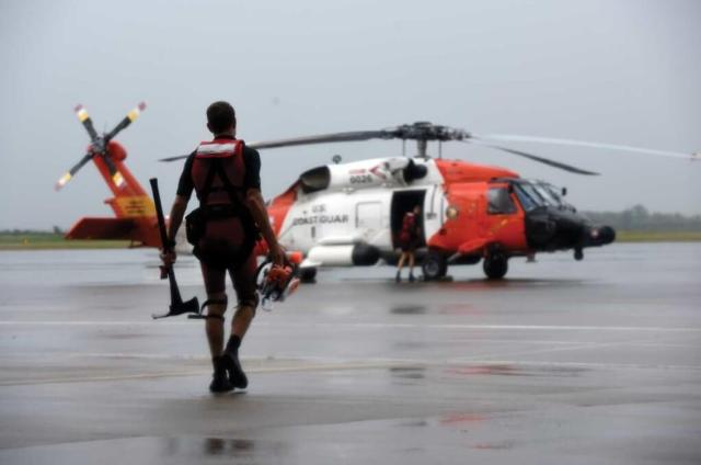 With an axe in one hand and a chainsaw in the other, a Coast Guard rescue swimmer walks to an MH-60 Jayhawk at Air Station Houston. U.S. Coast Guard Photo