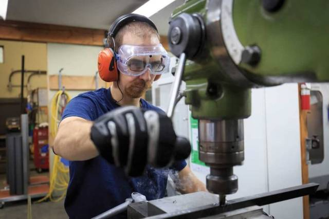 Doug Hammer operates a drill press.