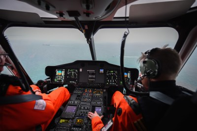 Two men sit in cockpit of helicopter