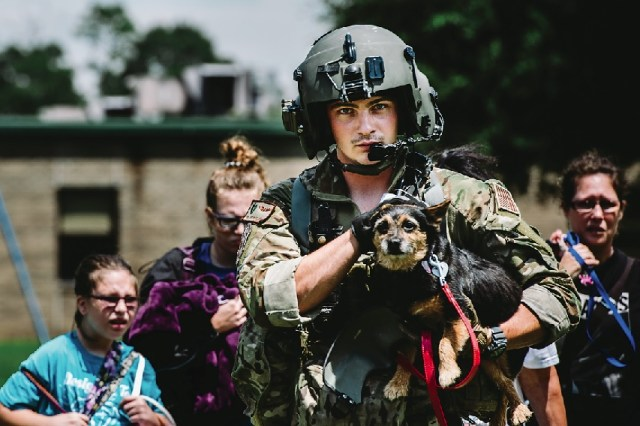 Senior Airman Austin Hellweg, 129th Rescue Squadron special missions aviator, carries a dog and leads a family into an HH-60 Pavehawk for extraction to a safer location during the relief effort for Hurricane Harvey, Aug. 31 in Beaumont, Texas. USAF SSGT Jordan Castelan Photo