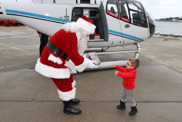 Santa giving out toys from an EC120 B at Coast Guard Station Southwest Harbor in Maine. Friends of Flying Santa Photo