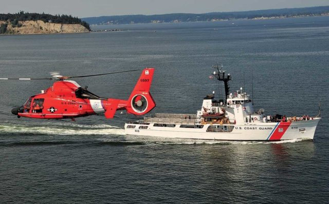 A MH-65D works around a USCG 210-foot cutter. The ships, boats, and aircraft of the USCG work together to keep the U.S. safe. Skip Robinson Photo