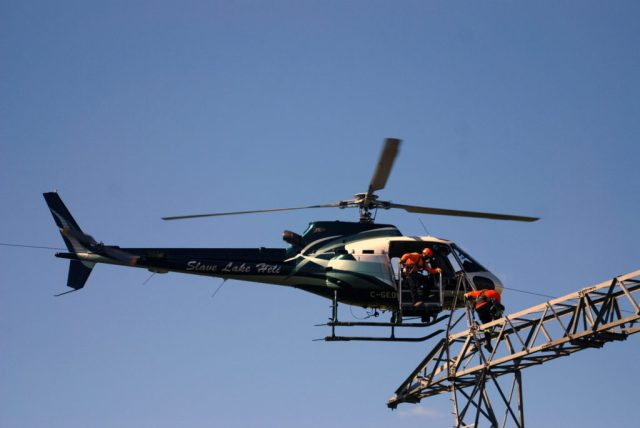 Slave Lake Helicopters Pilot Danny Ragan transfers powerline technicians. Slave Lake Helicopters Photo