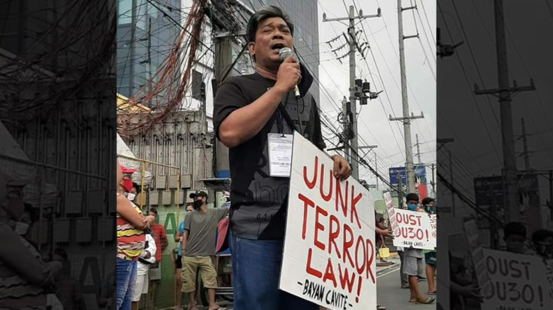 "A man stands with a protest sign reading ""Junk Terror Law!"" and holding a microphone."
