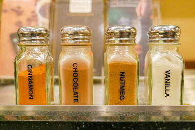 Starbucks condiment counter powder shakers: cinnamon, chocolate, nutmeg, vanilla