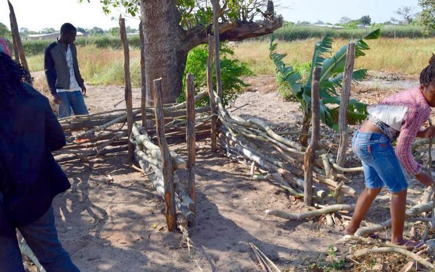 Eleverne i gang med at bygge beholderens sider. Til dette bruger de pinde og grene fundet på skolens område.