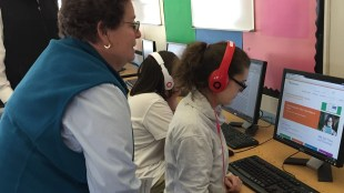 A teacher looking at a student who is using bookshare in audio format