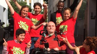 a group of people smiling. There is a person in the middle in a wheelchair.