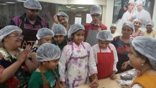a group of children inside a kitchen listening to baking instructions from an adult mentor.
