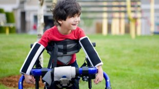 a young boy seen holding a crutches like support accessory and smiling