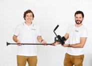 two men holding a KMINA crutch.