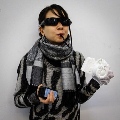 Emily gossiaux wearing brain port – the sunglasses with camera and an attachment that sits on her tongue, that lets her see through her tongue. She is seen holding a phone in her right hand and an object that looks like a camera in her left.
