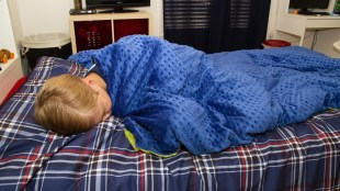 a child in bed with the weighted blanket wrapped around him.