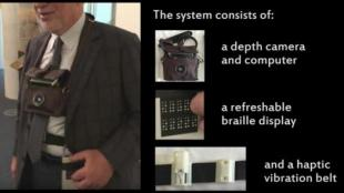 a blind person is seen wearing the 3d camera around his neck, and wearing the belt with haptic feedback as well as the refreshable braille display