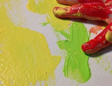 a child's hand seen covered in red paint and resting on a canvas that has yellow and green paint smudged on it.
