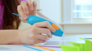 A child holding a 3Doodler 3Doodler pen and is about to start drawing.