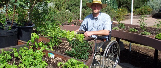 A man wearing a hat is seen in his wheelchair. In front of him are some plants. It looks like he is in a garden.