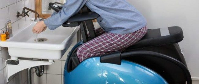 A woman seen sitting in the bathroom sitting in her Rodem mobility chair. She is leaning in to the wash basin and washing her hands.