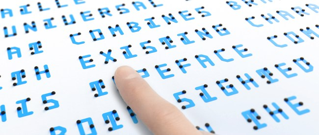 Close up of text in Braille Neue. A finger is seen on the text presumably of a blind person feeling the Braille bumps.