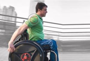 image showing a person pulling a rowheels revolution 1.0 wheelchair. There are circles drawn around his right shoulder indicating that is where pain and injury occurs from traditional wheelchairs that use the pushing action.
