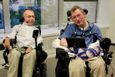 two tecla users in their wheelchair seen smiling at the camera