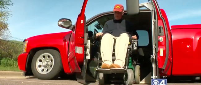 Phil seen getting out of his truck in his wheelchair. His modified Silverado uses his