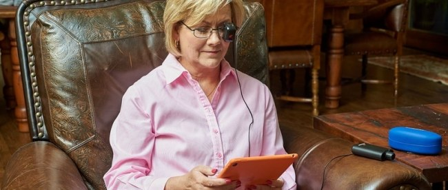 a woman seen sitting in a big leather chair, reading wearing seeBOOST and reading something on her tablet.