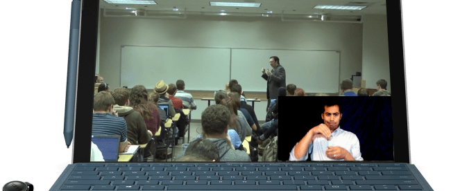a computer screen showing a class in session. A professor is seen teaching a class full of students. On the bottom right corner of this video is an overlay with an interpreter seen signing the professor in real time.