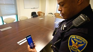 a San Francisco Police Department officer is seen holding his phone and interacting with a sign language interpreter through the app in order to provide better communication to deaf community members.