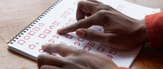photo shows a person's right hand tracing letters on a paper printed in ELIA
