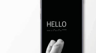 image of a samsung phone with the good vibes app interface. It displays the word hello in english and morse code. Someone's fingers are resting on the phone as if they just tapped the word.