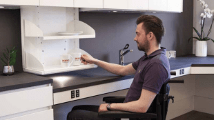 a man in a wheelchair seen grabbing a mug from a kitchen cabinet