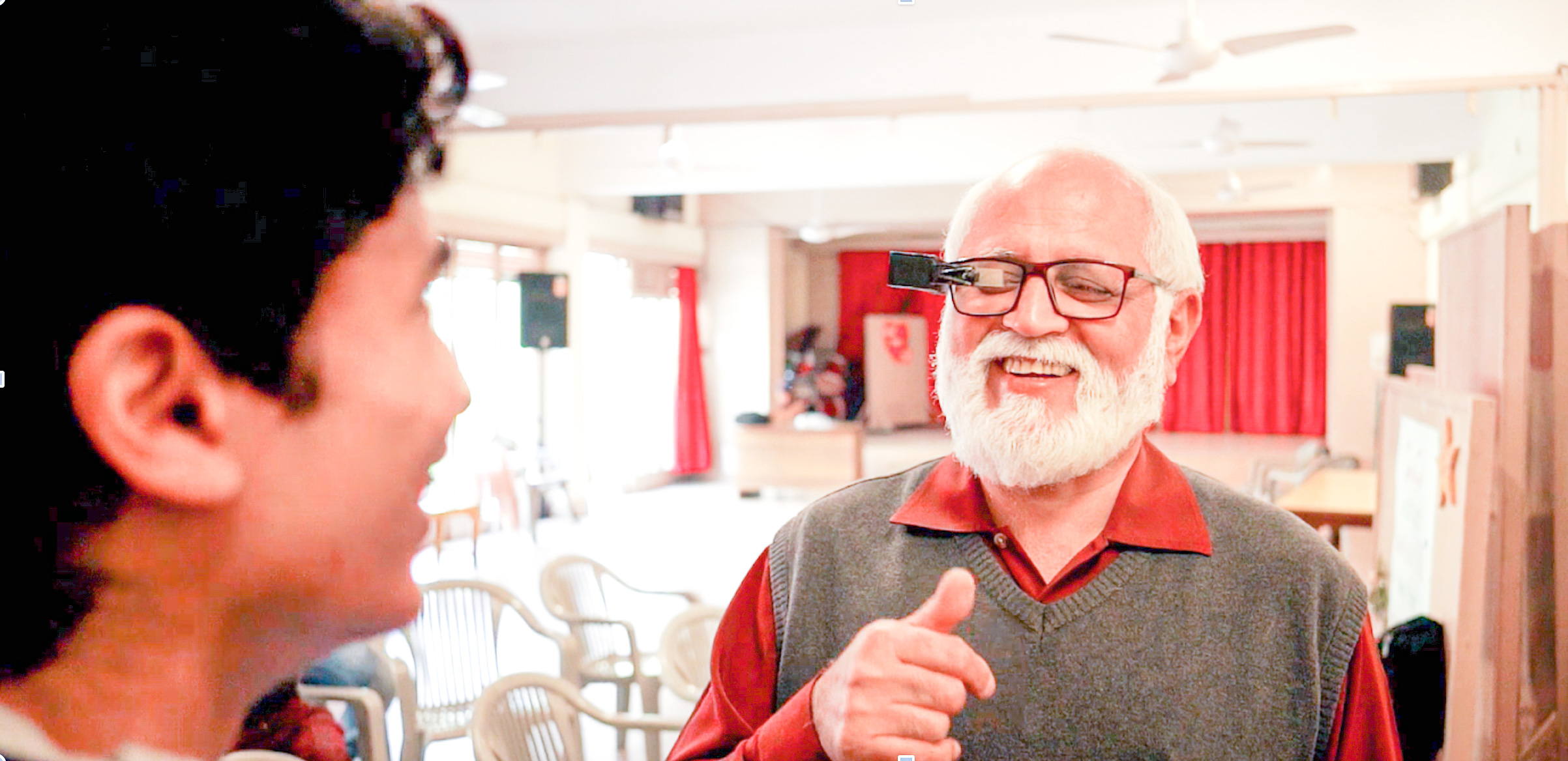 An older man seen interacting with another person and smiling. He is wearing glasses with TranscribeGlass attached to them.