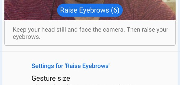 """A person setting up their android phone for facial gestures. Screen shows camera enabled with a blue box around his face with raised eyebrows with label """"raise eyebrows"""". There are some settings options in the bottom half."""